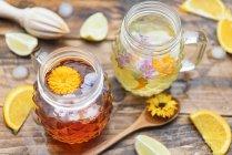 Refreshing mineral water with edible flowers, Viola wittrockiana, Dianthus caryophyllus, Calendula officinalis, lemon and orange — Stock Photo