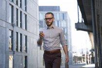 Homme d'affaires utilisant un téléphone portable tout en marchant dans la ville — Photo de stock