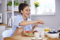 Femme souriante assise à table avec pastèque, jus d'orange — Photo de stock