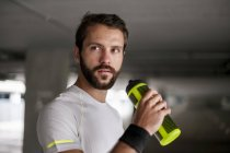 Athlete in parking garage holding drinking bottle — Stock Photo