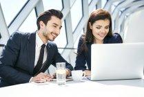 Donna d'affari sorridente e uomo d'affari che utilizza il computer portatile alla scrivania in un ufficio moderno — Foto stock