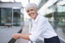 Retrato de mujer mayor feliz apoyada en barandilla en la ciudad - foto de stock
