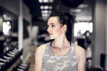 Спортивная женщина в спортзале смотрит сбоку — стоковое фото