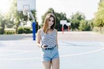 Портрет молодой женщины на спортивной площадке с сотовым телефоном — стоковое фото