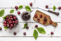 Jar of cherry jam and cherries on white wood — Stock Photo