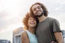 Retrato de pareja feliz a orillas del río al atardecer - foto de stock