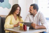 Молода жінка і людина обмін планшета в кафе — стокове фото