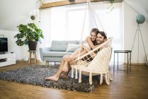 Happy affectionate couple sitting in hanging chair at home — Stock Photo