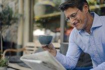 Empresário maduro sentado no café, bebendo café — Fotografia de Stock