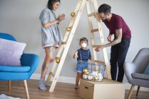 Modern family decorating the home at Christmas time using ladder as Christmas tree — Stock Photo