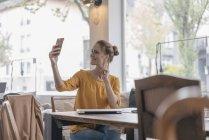 Молодая женщина сидит в коворкинге, делает селфи на смартфоне — стоковое фото