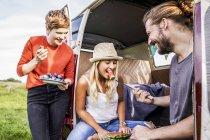 Счастливые друзья едят арбуз в фургоне — стоковое фото