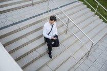 Homme d'affaires avec téléphone portable descendant — Photo de stock