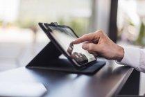 Primer plano del hombre de negocios utilizando la tableta en un café - foto de stock