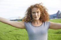 Портрет улыбающейся молодой женщины, стоящей на лугу летом — стоковое фото