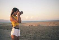 Teenage girl taking photo with camera on beach at sunset — Stock Photo