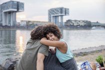 Happy couple relaxing at riverside at sunset — Stock Photo