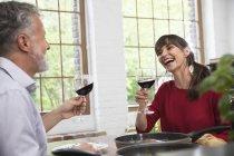 Счастливая пара, сидящая на кухне, пьющая красное вино, наслаждающаяся ужином — стоковое фото