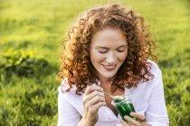 Портрет улыбающейся молодой женщины, поедающей желе на лугу — стоковое фото