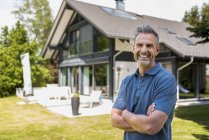 Portrait of happy mature man in garden of his home — Stock Photo