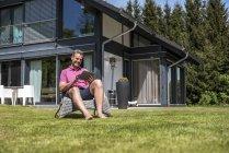 Улыбающийся зрелый мужчина сидит в саду своего дома с помощью планшета — стоковое фото
