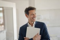 Successful businessman standing in office with laptop — Stock Photo