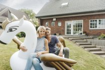 Portrait of smiling mature couple sitting on inflatable pool toy in garden of house — Stock Photo