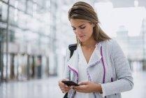 Giovane donna che usa il cellulare in aeroporto — Foto stock