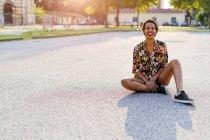 Retrato de la joven que ríe sentada en la carretera al aire libre al atardecer - foto de stock