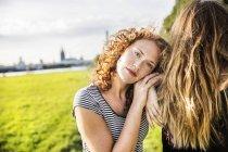 Портрет рыжеволосой молодой женщины, опирающейся на друга на зеленом лугу — стоковое фото