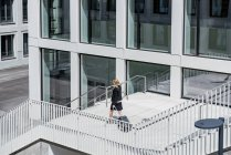 Підприємець з чемодан і кава йти ходити перед офісними будівельними — стокове фото