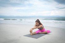 Femme pratiquant le yoga sur la plage — Photo de stock