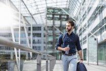 Молодой бизнесмен на ходу в здании со стеклянным фасадом — стоковое фото
