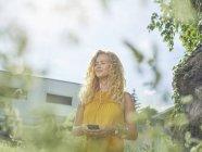 Улыбающаяся молодая женщина с мобильным телефоном и наушниками на улице — стоковое фото