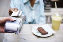 Frau bezahlt mit Kreditkarte im Straßencafé, Nahaufnahme — Stockfoto