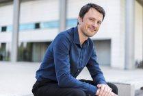 Retrato de um empresário sorridente sentado ao ar livre — Fotografia de Stock