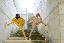 Два альтернативных друга позируют на ступеньках, одетые в желтые и розовые джинсы — стоковое фото