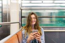Ritratto di giovane donna sorridente in treno sotterraneo che guarda lo smartphone — Foto stock