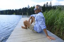 Germany, Mittenwald, mature man sitting and relaxing on jetty at lake — Stock Photo
