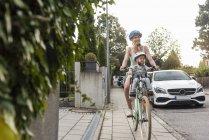 Мати і дочка їзда на велосипеді, дочка носіння шолом і сидячи в дитячому кріслі — стокове фото