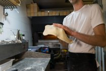 Close-up of pizza baker preparing pizza dough in kitchen — Stock Photo