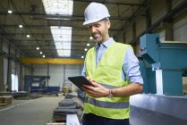 Smiling man wearing shirt and safety vest using tablet in factory — Stock Photo
