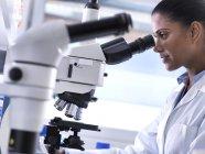 Recherche en biotechnologie, chercheuse examinant un spécimen au microscope en laboratoire — Photo de stock