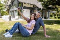 Счастливая пара, сидящая в саду своего дома, делает селфи — стоковое фото