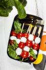 Обед поле нанизаны помидоры черри и моцарелла сыр шары с листьями базилика и винегрет — стоковое фото