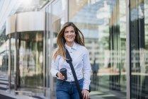 Giovane donna d'affari sorridente con borsa e caffè da portare via — Foto stock