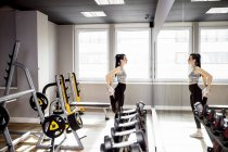 Жінка гімнастика у тренажерному залі, дивлячись у дзеркало — стокове фото