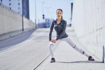 Femmina corridore stretching gambe durante l'allenamento urbano — Foto stock