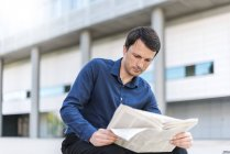 Businessman reading newspaper in the city — Stock Photo
