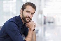 Портрет уверенного молодого бизнесмена, сидящего в зале ожидания — стоковое фото